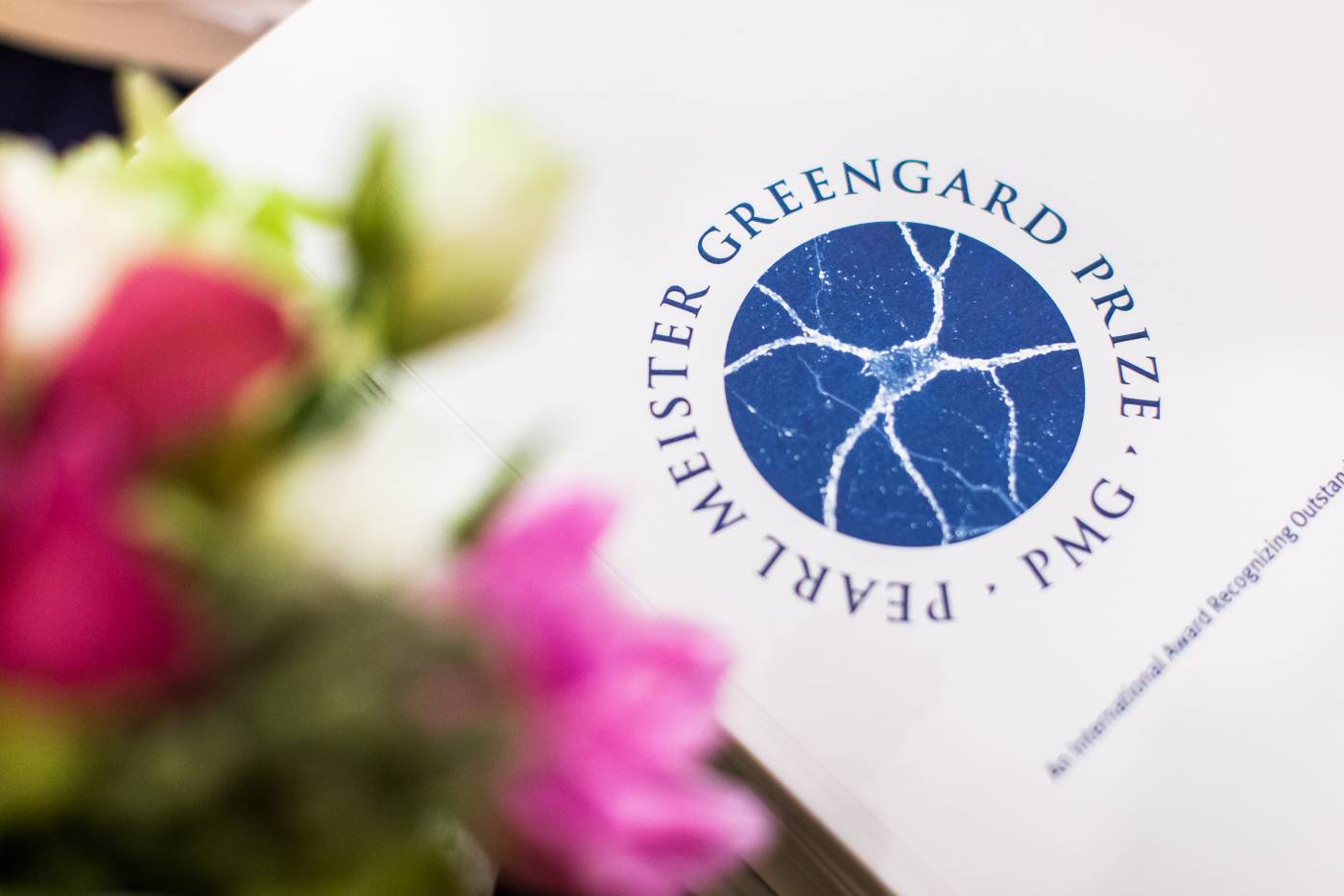 Pearl Meister Greengard Prize logo printed on paper, out of focus flower on left