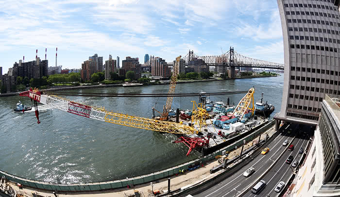 Ready to lift: The barge-mounted crane that will lift the prefabricated modules of the River Campus into place over FDR Drive arrives at Rockefeller.