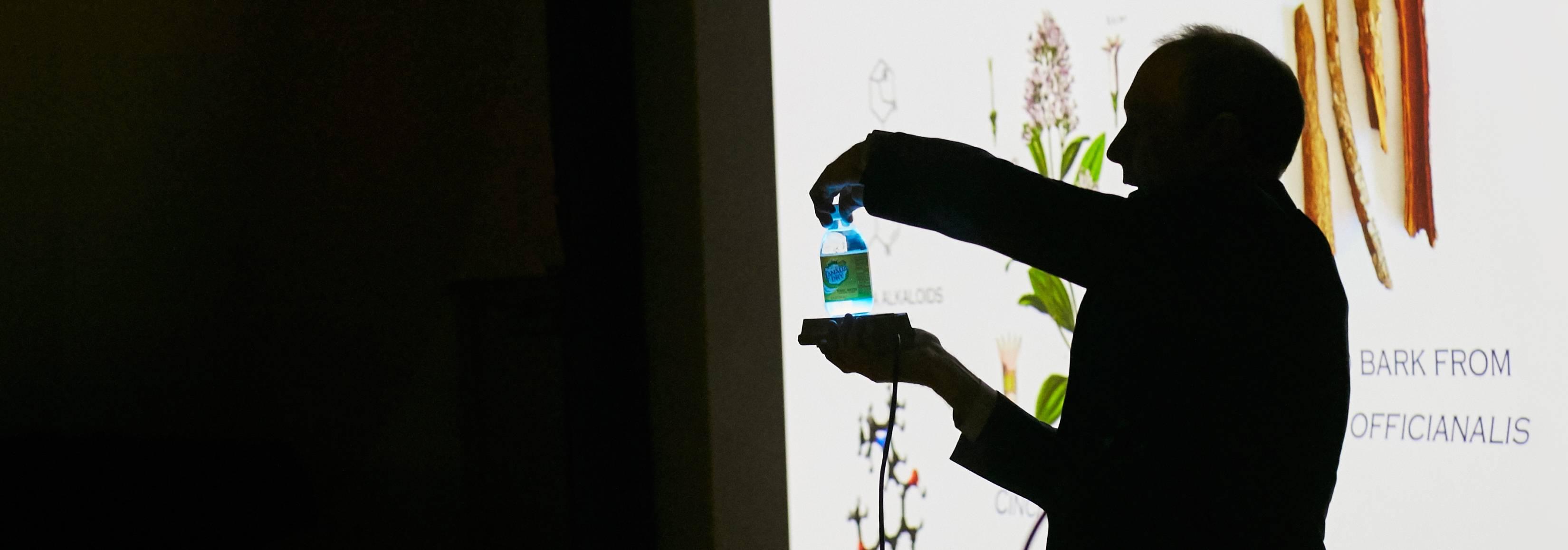 Silhouette of scientist shining blue light under liquid in bottle